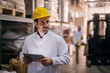 Picture of young focused male manager standing in factory and holding tablet. Dressed in white coat with helmet on his head. Looking satisfied and proud.
