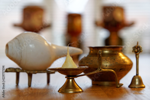 Ghee candle, conch shell with brass bell and water pot, Hindu deity Lord Jagannath in the blurry background