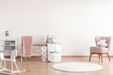 Bright scandinavian baby room with rocking horse, white nursery and pink armchairs, posters on the wall