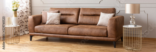 Obraz Panoramic view of brown leather sofa between two stylish tables with marble tops, real photo - fototapety do salonu