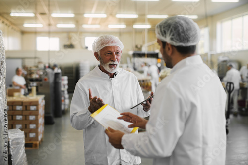Fotografia  Two serious business man in sterile clothes standing in food factory and talking about business