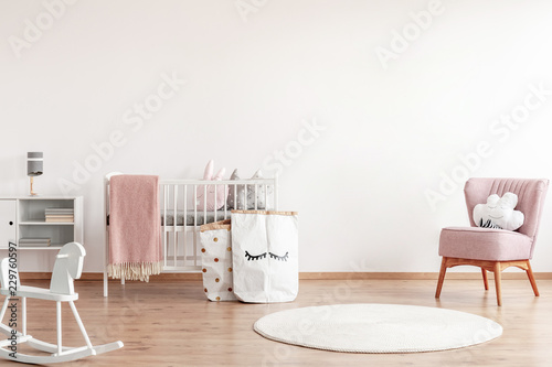 Fotografia  Bright scandinavian baby room with rocking horse, white nursery and pink armchai
