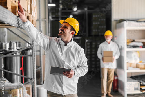 Picture of smiling young man warehouse worker counting boxes in warehouse. Holding digital tablet in his hands.