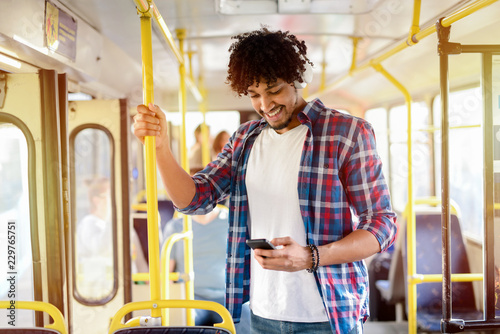 Fotografie, Obraz  Young modern Afro-American man standing in a public transport and listening to the music