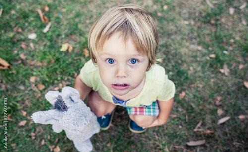 Valokuva niño agachado con peluche en la mano mirando hacia arriba