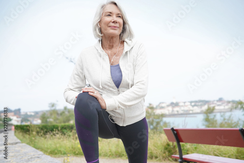 Senior woman stretching outdoors before running Canvas Print