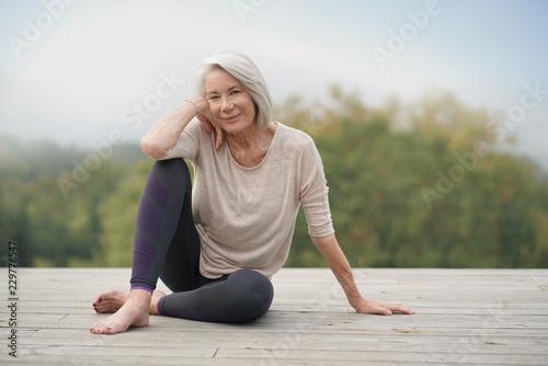 Stampa su Tela Beautiful elderly woman sitting outdoors in sportswear