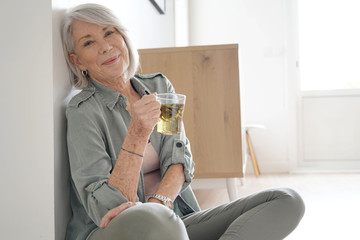 Fototapeta Attractive senior woman sitting on the floor at home with tea