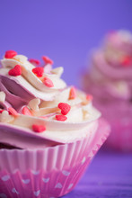 Closeup Two Cupcakes With Creamy Pink And White Top Decorated With Little Hearts On Purple Background.