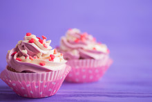 Closeup Two Cupcakes With Creamy Pink And White Top Decorated With Little Hearts On Purple Wooden Background.