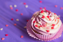 Closeup Cupcake With Creamy Pink And White Top Decorated With Little Hearts On Purple Background