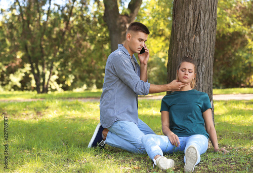 Passerby calling ambulance while checking pulse of unconscious woman outdoors Canvas Print