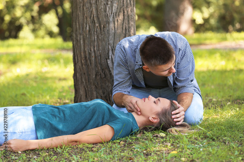 Photo Man checking for breathing of unconscious woman outdoors