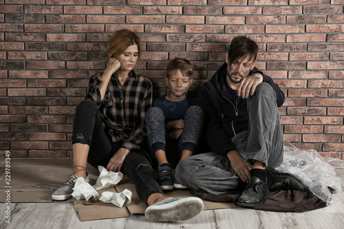 Fotografija  Poor homeless family sitting on floor near brick wall