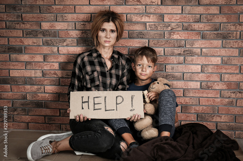 Valokuva  Poor woman with her son asking for help near brick wall
