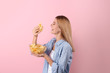 Woman eating potato chips on color background