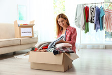 Woman Packing Clothes Into Don...