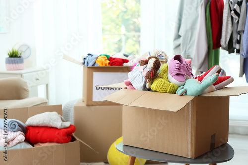 Photo Donation box with clothes and toys on table indoors