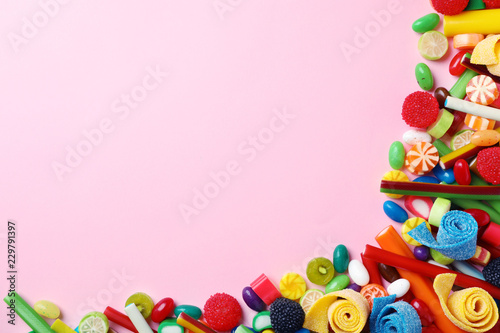 Poster Confiserie Flat lay composition with delicious colorful candies and space for text on color background