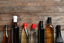 Bottles With Different Kinds Of Vinegar And Space For Text On Wooden Background, Flat Lay