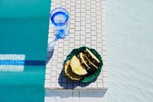 A Bowl Of Pineapple And A Drink By A Pool