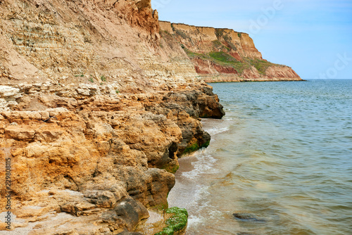 beautiful sea landscape, closeup of stone on the beach, sea coast with high hills, wild nature