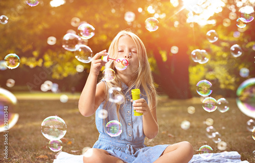 Fototapeta Portrait of a cheerful girl blowing soap bubbles obraz