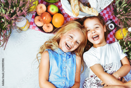 Acrylic Prints Artist KB Two cheerful kids lying on a picnic blanket among refreshments