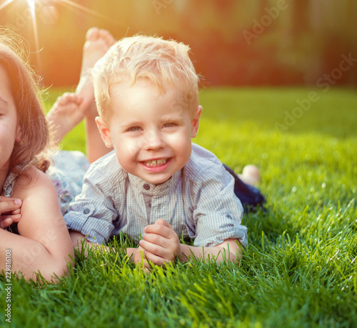 Acrylic Prints Artist KB Cheerful siblings relaxing on a fresh lawn