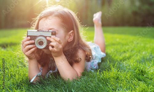 Acrylic Prints Artist KB Cute little girl lying on green lawn and taking a picture