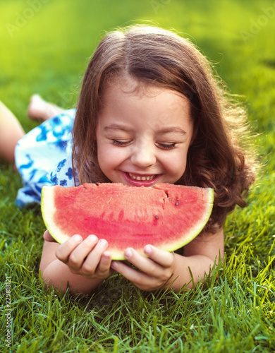 Acrylic Prints Artist KB Closeup portrait of smiling girl holding watermelon slice in the garden