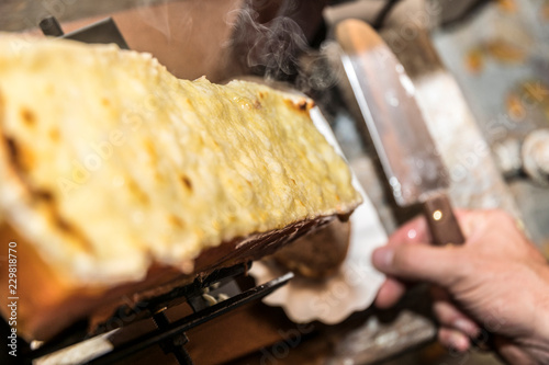 raclett cheese with hand and knife