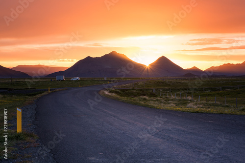 Amazing summer sunset landscape, Iceland. Scenic road to the mountains and sun, travel background