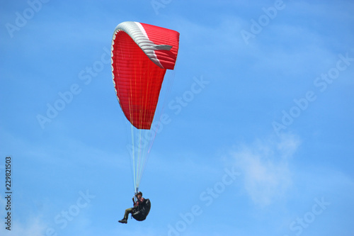 Paraglider flying red wing