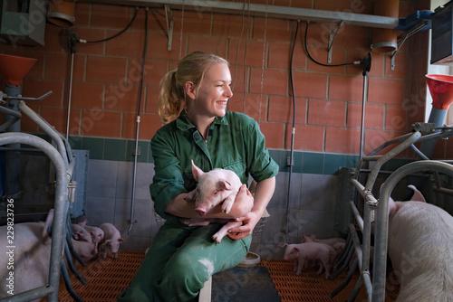 Spass am Beruf, junge Landwirtin im Stall mit Ferkel im Arm