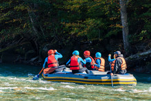 Group Of Young People Going White Water Rafting
