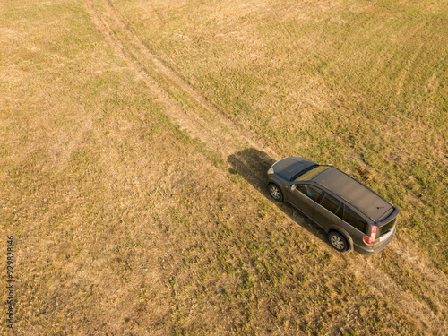 Fototapeta aerial top view of car isolated on summer field texture background f