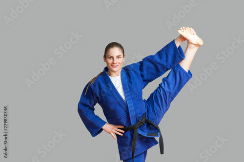 Deurstickers Vechtsport Beautiful happy athletic karate woman in blue kimono with black belt making vertical twine and looking at camera with toothy smile. Japanese martial arts concept. Indoor, studio shot, gray background