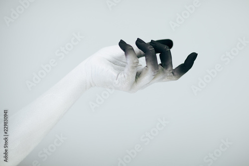 Creepy Halloween monster hand with white and black make up in front of white bac Wallpaper Mural