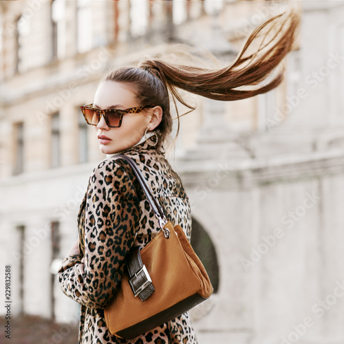 Outdoor close up fashion portrait of young beautiful fashionable woman wearing sunglasses, leopard print blazer, hoop earrings, holding brown suede bag, walking in street of european city. Copy space
