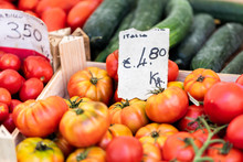 Closeup Of Many Ripe Red, Yellow, Heirloom Tomatoes On Display Farmers Market Shop Store Grocery Italy In Wooden Crates Boxes With Sign, Price
