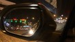 Night shot of a view through the car mirror. Looking at the cars passing by in a low traffic avenue.