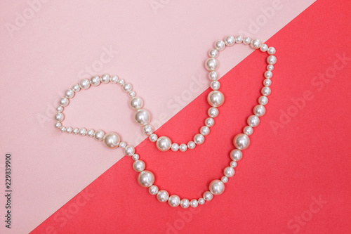 Foto  Shiny pearl necklace on pink background