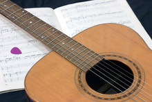 Acoustic Guitar On The Background Of A Music Book With Notes And Pick