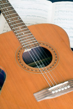 Acoustic Guitar On The Background Of A Music Book With Notes