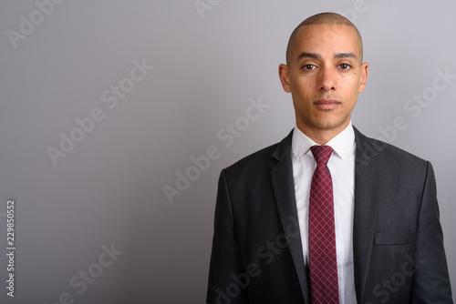 Fotografie, Obraz Handsome bald businessman wearing suit against gray background