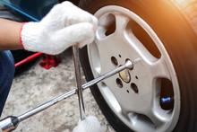 Mechanic Hands Change A Car Tyre On Street