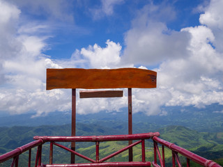 Blank of wooden billboard for advertisement with moutains and sky cloudy background.