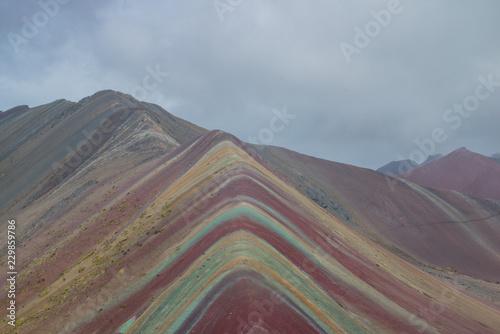 Poster Vinicunca, also called Montaña de Siete Colores, Montaña de Colores or Rainbow Mountain, in a cloudy day, in Perù.
