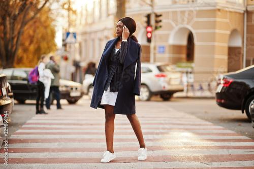 fototapeta na lodówkę Success stylish african american woman in coat walking at crosswalk.